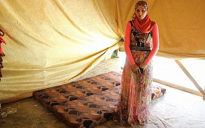 Fadia Ammar Al Mohamad, who didn't meet her husband until the day of their wedding, stands next to the cot they sleep on in their tent. (L Marie/ Times of Israel)