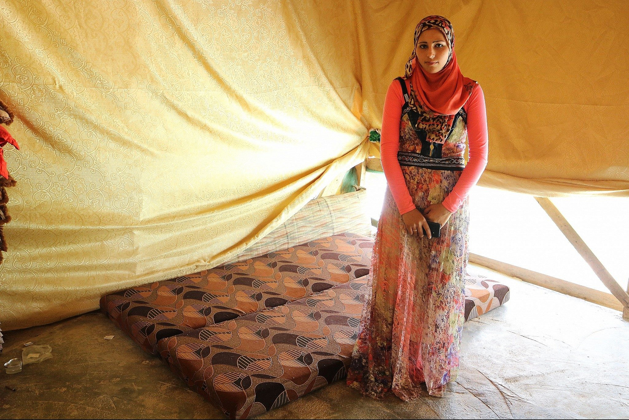 Fadia Ammar Al Mohamad, who didn't meet her husband until the day of their wedding, stands next to the cot they sleep on in their tent. (Lisa Khoury/ Times of Israel)