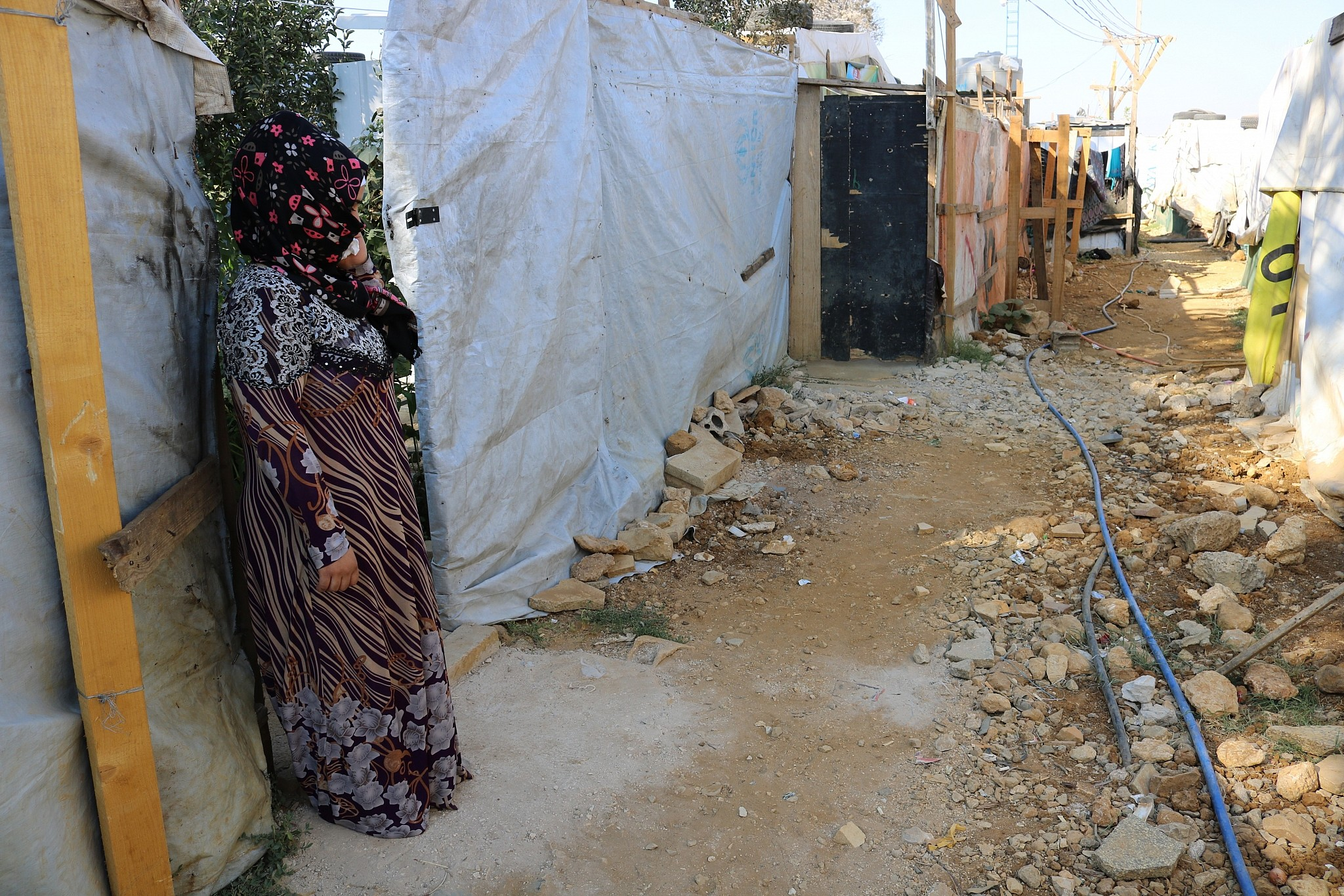 Halima Ali Al Hussein stands outside her family's hut, which she's barely allowed to leave. After getting divorced, she's considered a shame to the community. (Lisa Khoury/ Times of Israel)