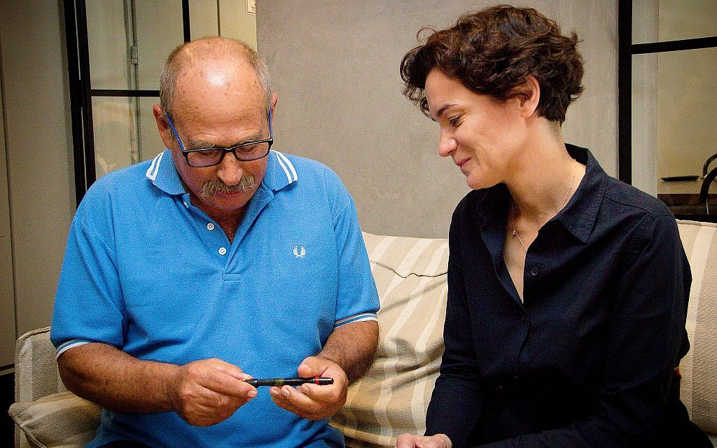 Yaron Roksa (left) receives pen that was confiscated from his father by the Nazis from ITS director Floriane Hohenberg, Jaffa, July 3, 2018. (Laura Ben-David/Courtesy of ITS)