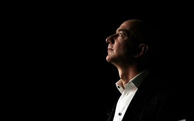 Jeff Bezos, CEO and founder of Amazon, is illuminated by a display screen at the introduction of the new Amazon Kindle Fire HD and Kindle Paperwhite in Santa Monica, California, Thursday, September 6, 2012. (AP Photo/Reed Saxon)