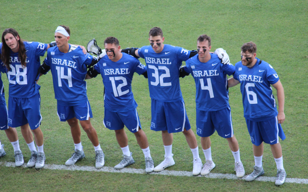 Members of Israel's national lacrosse team sway to the country's national anthem before a game at the World Lacrosse Championship in Netanya, Israel, July 2018.  (Hillel Kuttler via JTA)