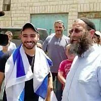 Elor Azaria (L), who was convicted and jailed for killing a wounded Palestinian in the West Bank city of Hebron in March 2016, smiles as he visits Hebron as a free man in July 3, 2018. Standing next to him is far-right activist Baruch Marzel. (Screen capture/Haverim Laset Tzara organization)