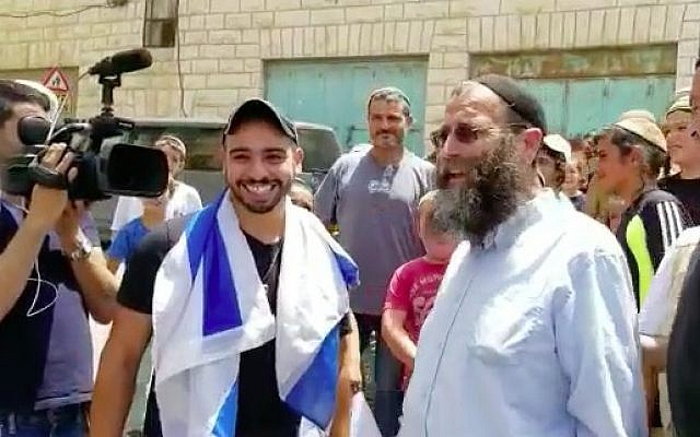 Elor Azaria (r) smiles next to far-right activist Baruch Marzel in his return to Hebron on July 3, 2018. (Screen capture/Haverim Laset Tzara organization)