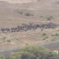 Displaced Syrians approach the Israeli border in an apparent attempt to get help as dictator Bashar Assad's forces close in on them on July 17, 2018. (Screen capture: Reuters)