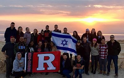 Above and main picture: Students on a Rutgers trip to Israel financed by the Maccabee Task Force pose against the background of sunrise over Masada (Courtesy)