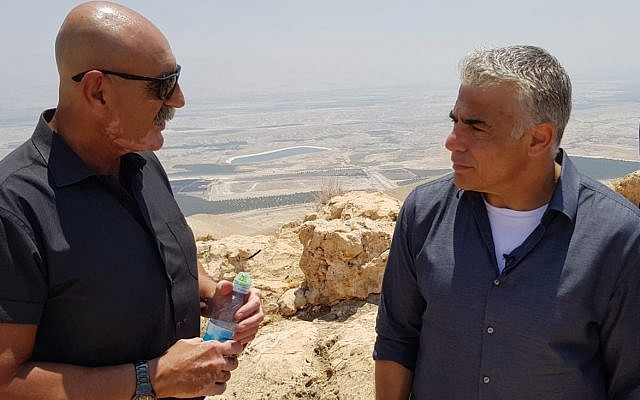 Jordan Valley Regional Council chairman David Elhayani (L) speaks to Yesh Atid chairman Yair Lapid at a lookout point above the Jordan Valley on July 23, 2018. (Courtesy)