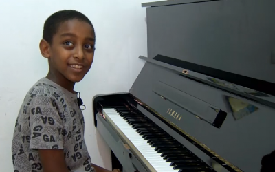 10-year-old Oshri Bitau at his new piano in the family's Nazareth Illit home, July 15, 2018. (Hadashot screen capture)