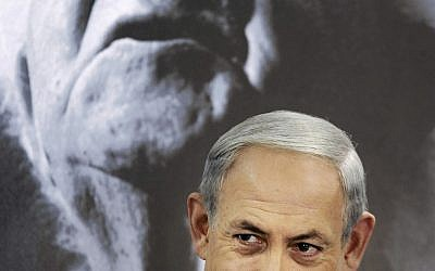 Prime Minister Benjamin Netanyahu chairs a cabinet meeting at Kibbutz Sde Boker, Israel, Sunday, Nov. 10, 2013. A portrait of the first Israeli prime minister David Ben Gurion is seen at background. (AP Photo/David Buimovitch, Pool)