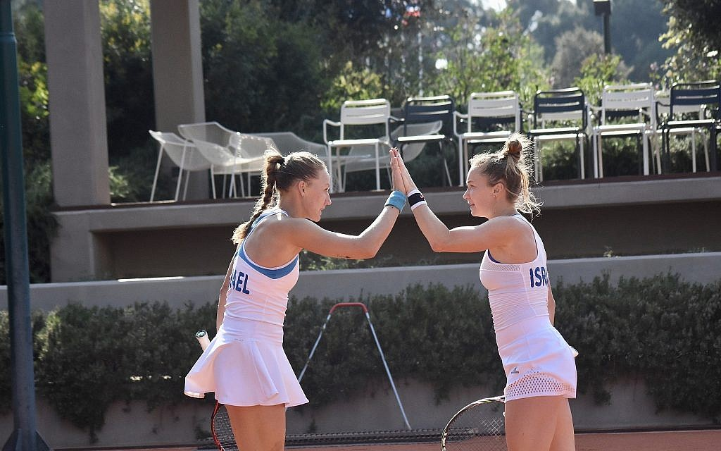 Julia Glushko, left, and sister Lina high five on the court. (Ofra Friedman/ITA)