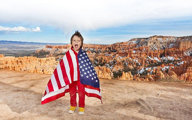 Laughing small boy with open mouth bundled up into American flag, Bryce Canyon National Park, USA