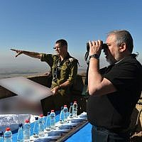 Defense Minister Avigdor Liberman peers through binoculars on a hilltop overlooking the border with Syria as Brig. Gen. Amit Fisher gives him a briefing on developments in the area, on July 10, 2018. (Ariel Hermoni/Defense Ministry)