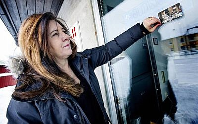 Carinne Sjoberg peeling off a sticker that neo-Nazis left on the door of what used to be the Jewish community center of Umea, Sweden. (Courtesy of Sjoberg/via JTA)