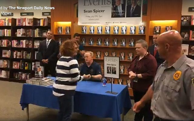 Former White House press secretary Sean Spicer (seated) at a book signing event in Newport News on July 27, 2018. (Screen capture: Facebook)