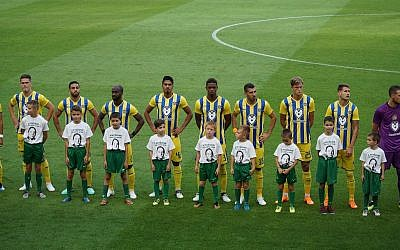 Hungarian children standing with Maccabi TLV players in tribute to Holocaust hero István Tóth at Groupama Arena in Budapest, July 12 2018. (Courtesy/ World Jewish Congress)