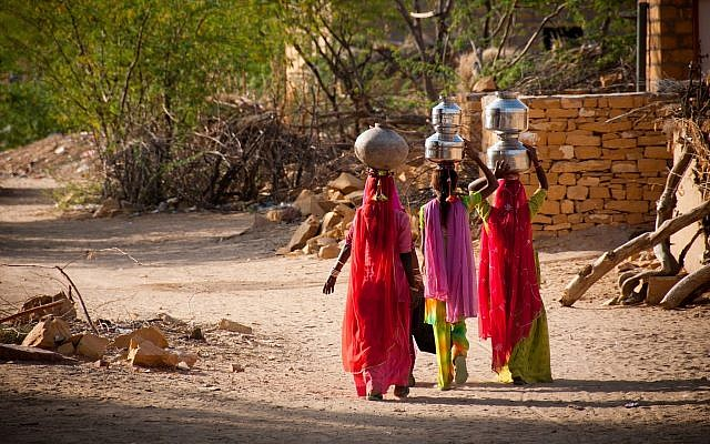 Illustrative image of women carrying water in a village in India (FrankCornfield; iStock by Getty Images)