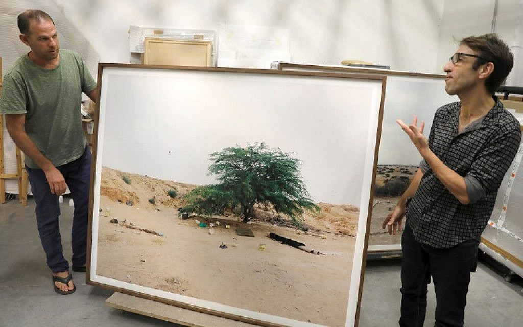 "Art photographer Ron Amir (L) and curator Noam Gal stand next to a picture from the exhibition on migrants, ""Somewhere in the Desert,"" at the Israel Museum storage room in Jerusalem on July 2018. (AFP Photo/Menahem Kahana)"