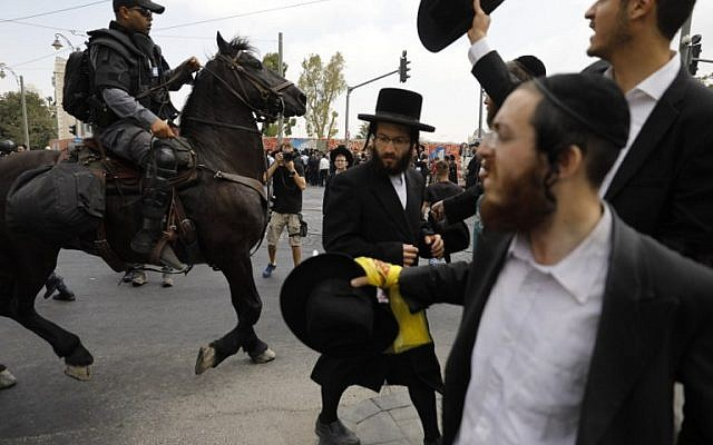 A member of the Israeli mounted police unit tries to disperse a demonstration of ultra-Orthodox protesting against the arrest of a draft dodger in Jerusalem on August 2, 2018. (AFP PHOTO / Menahem KAHANA)
