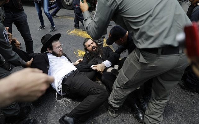 Ultra-Orthodox Jew, demonstrating against the annual Gay Parade, scuffle with Israeli security forces in Jerusalem on August 2, 2018.  The 17th edition of Gay Pride in the holy city, was held under heavy police surveillance, the murder of a 16-year-old girl, stabbed to death by an ultra-Orthodox Jew during the 2015 parade, remaining very present in the minds.  / AFP PHOTO / MENAHEM KAHANA