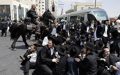 A member of the Israeli mounted police unit tries to disperse a demonstration of ultra-Orthodox men protesting against the arrest of a draft dodger in Jerusalem on August 2, 2018. (AFP Photo/Menahem Kahana)