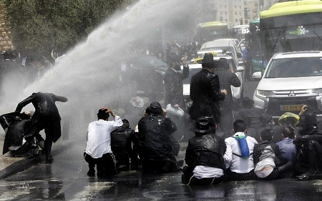 Ultra-Orthodox Jewish men are sprayed with water cannons by Israeli security forces protesting against the arrest of a draft dodger in Jerusalem on August 2, 2018. (AFP PHOTO / Menahem KAHANA)