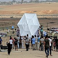 Palestinians prepare to fly a kite near the Gaza border with Israel, east of Jabalia, on August 3, 2018. (AFP/ MAHMUD HAMS)