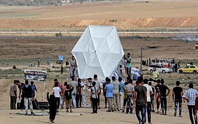 Palestinians prepare to fly a kite near the Gaza border with Israel, east of Jabalia, on August 3, 2018. (AFP/ MAHMUD HAMS)