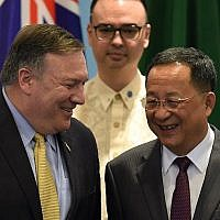 US Secretary of State Mike Pompeo (L) chats with North Korea's Foreign Minister Ri Yong Ho (R) as Philippine Foreign Secretary Alan Peter Cayetano (behind) looks on, as they arrive for a group photo at the ASEAN Regional Forum Retreat during the 51st Association of Southeast Asian Nations (ASEAN) Ministerial Meeting (AMM) in Singapore on August 4, 2018. (AFP PHOTO / MOHD RASFAN