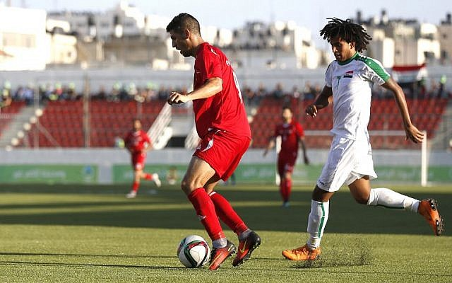Palestine's Tamer Syam, left and Iraq's Mazin Fyad vie for the ball during the friendly soccer match between Palestine and Iraq at the Faisal al-Husseini stadium in the West Bank town of al-Ram on August 4, 2018. (AFP/ABBAS MOMANI)