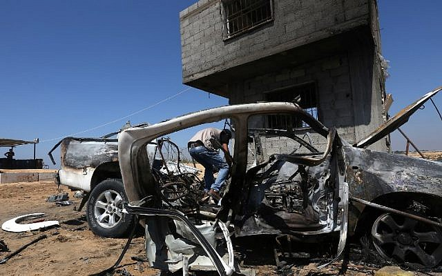 A Palestinian man inspects a damaged car after an Israeli airstrike on Beit Lahya, northern gaza strip, on August 5, 2018. (AFP/ MAHMUD HAMS)