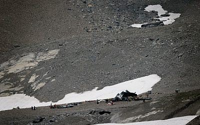 Accident investigators and rescue personnel gather around the wreckage of a Junkers JU52 aircraft at Flims on August 5, 2018, after the airplane crashed into Piz Segnas, a 3,000-meter (10,000-foot) peak in eastern Switzerland on August 4. (AFP PHOTO / Fabrice COFFRINI)