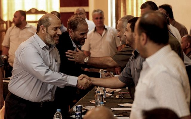 Hamas officials Husam Badran (2nd-L) and Khalil al-Hayya (L) arrive for a meeting with Palestinian factions in Gaza City on August 5, 2018. (AFP PHOTO / MAHMUD HAMS)