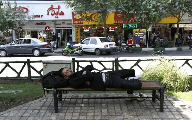 A man takes a nap on a bench in the Iranian capital Tehran on August 6, 2018. (AFP/ATTA KENARE)