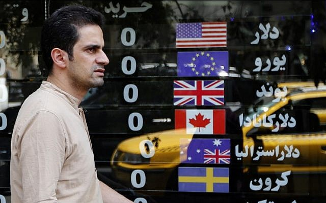 An Iranian man walks in front of a currency exchange shop in the Iranian capital Tehran on August 8, 2018. (AFP/Atta Kenare)