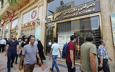 People walk in front of a currency exchange shop in the Iranian capital Tehran on August 8, 2018. (AFP PHOTO / ATTA KENARE)
