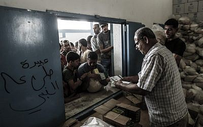 Palestinians receive aid at a United Nations food distribution center in the Jabaliya refugee camp in the northern Gaza Strip on August 8, 2018. (AFP Photo/Mahmud Hams)