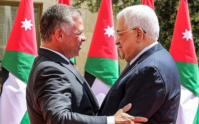 Palestinian Authority President Mahmoud Abbas (R) embraces King Abdullah II of Jordan as he arrives to meet with him at the Royal Palace in the capital Amman on August 8, 2018. (AFP/Pool/Khalil Mazraawi)