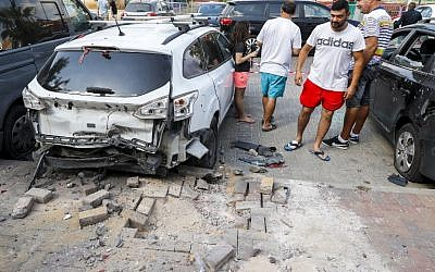 People stand next to a car that was damaged after a rocket fired by terrorists from the Gaza Strip fell in the southern Israeli town of Sderot on August 9, 2018. (JACK GUEZ/AFP)