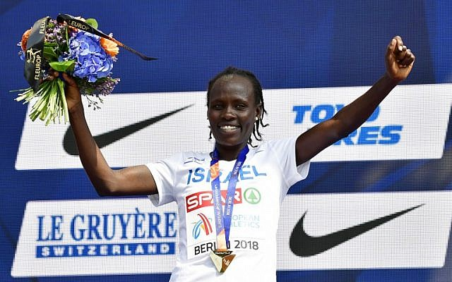 Winner Israel's Lonah Chemtai Salpeter celebrates on the podium with her medal during the medal ceremony of the women's 10000m event during the European Athletics Championships in Berlin on August 9, 2018. (AFP PHOTO / Tobias SCHWARZ)