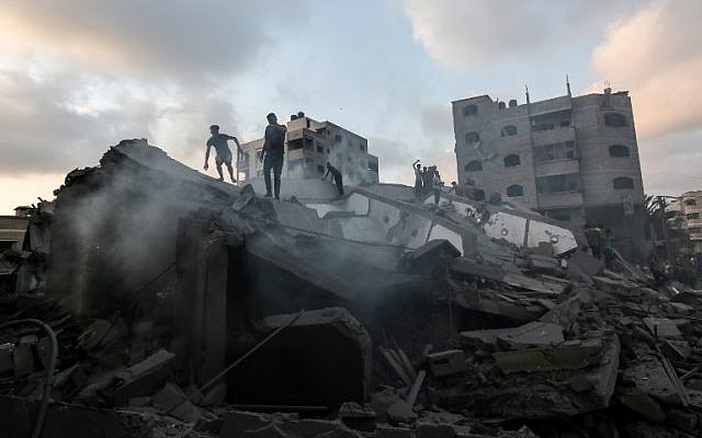 A picture taken on August 9, 2018, shows people inspecting the rubble of a building targeted by the Israeli Air Force in response to a rocket attack that hit southern Israel earlier in the day on August 9, 2018. (AFP Photo/Mahmud Hams)