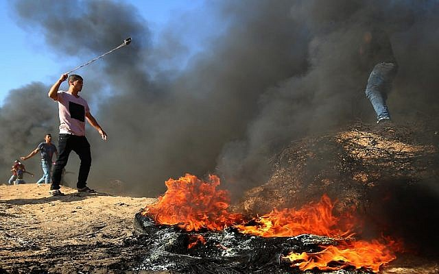 A Palestinian uses a slingshot during clashes along the border between Israel and the Gaza Strip, in the southern Gaza city of Khan Younis, on August 10, 2018. (AFP Photo/Said Khatib)