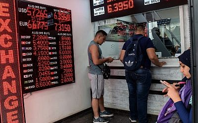 People check currency exchange rates at a currency exchange office on August 11, 2018 in Istanbul. (AFP/ Yasin AKGUL)