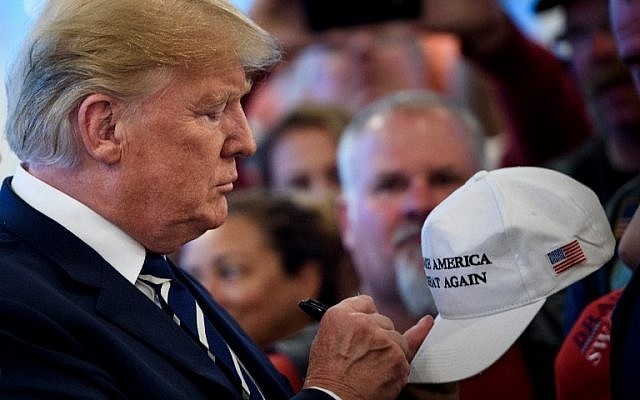 US President Donald Trump signs a hat while meeting with supporters during a Bikers for Trump event at the Trump National Golf Club in Bedminster, New Jersey on August 11, 2018. (AFP/Brendan Smialowski)