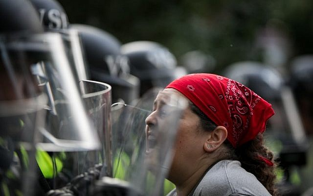 An activist confronts Virginia State Troopers in riot gear during a rally on the campus of The University of Virginia one year after the violent white nationalist rally that left one person dead and dozens injured in Charlottesville, Virginia on August 11, 2018. (AFP PHOTO / Logan Cyrus)