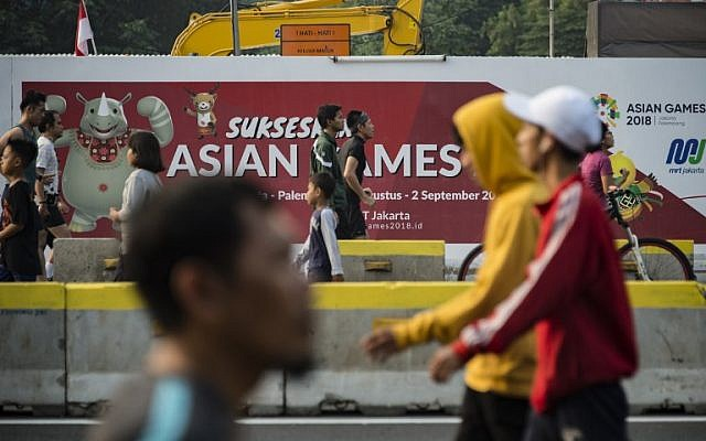 People exercise next to a banner for the 2018 Asian Games during a car-free day in Jakarta on August 12, 2018. (AFP PHOTO / BAY ISMOYO)