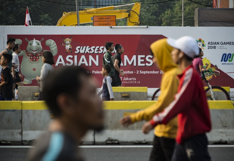 People Exercise Next To A Banner For The  Asian Games During A Car Free
