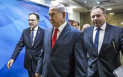 Prime Minister Benjamin Netanyahu, center, arrives ahead of the weekly cabinet meeting at his office in Jerusalem, August 12, 2018. (Jim Hollander/AFP)