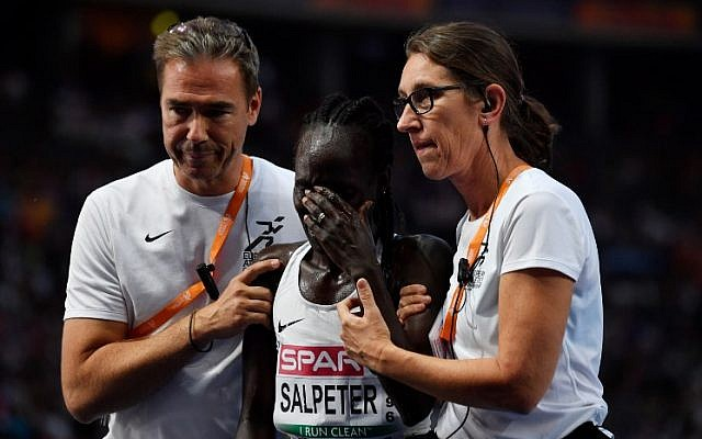 Runner Lonah Chemtai Salpeter is consoled after she miscounted the laps and stopped running too early in the women's 5000m final race during the European Athletics Championships at the Olympic stadium in Berlin, on August 12, 2018.  (John MacDougall/AFP)