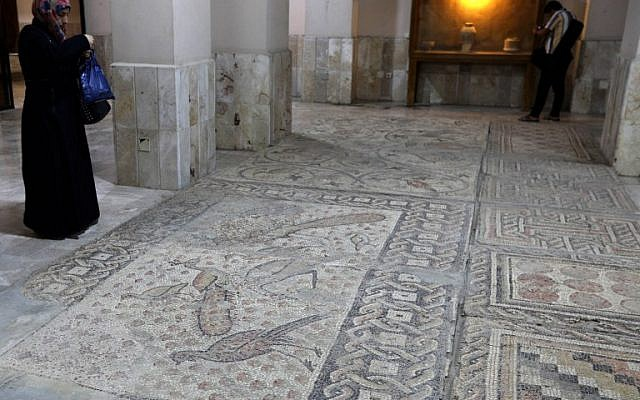 A Syrian woman takes pictures of mosaic on the floor of the Idlib Museum after it reopened on August 13, 2018 in the northern Syrian city of Idlib. (AFP PHOTO / OMAR HAJ KADOUR)