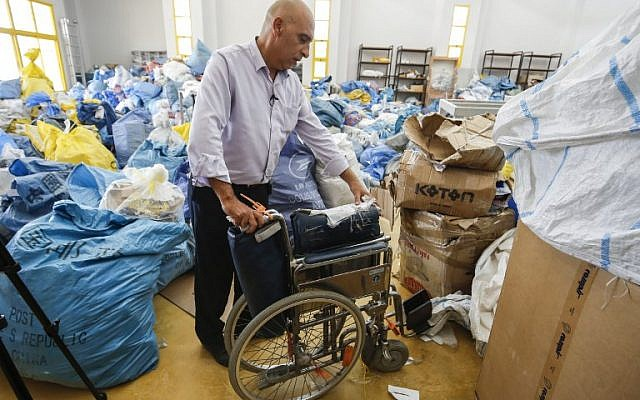 Ramadan Ghazawi, a Palestinian official at the central international exchange post office in the city of Jericho in the  West Bank, stands next to a folded wheelchair, one of many items of previously undelivered mail dating as far back as 2010 which has been withheld by Israel, at the premises in Jericho on August 14, 2018. (AFP / ABBAS MOMANI)